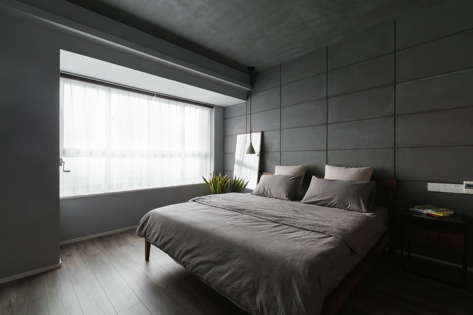 简约舒适的格调充满了整个卧室,黑色的墙面搭配原木花纹,是一个能让人感觉到舒适自然的温暖空间