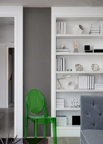 内陷的墙柜为客厅额外增加了收纳功能。蜂巢毛地毯的平面几何形态,呼应了柜架上无处不在的立体几何摆件。