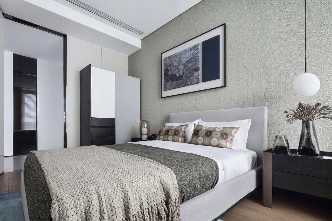 側臥配色素雅,床頭吊燈及挂畫設計,讓空間更顯時尚和前衛,視覺感受層次分明。
