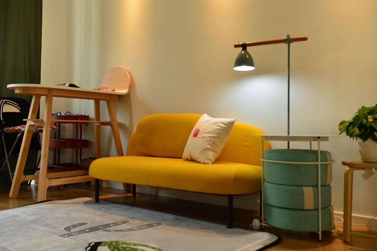 客厅的沙发没有选择中规中矩的L型或一字型,而是用一个小巧而且色彩明亮的小沙发代替。