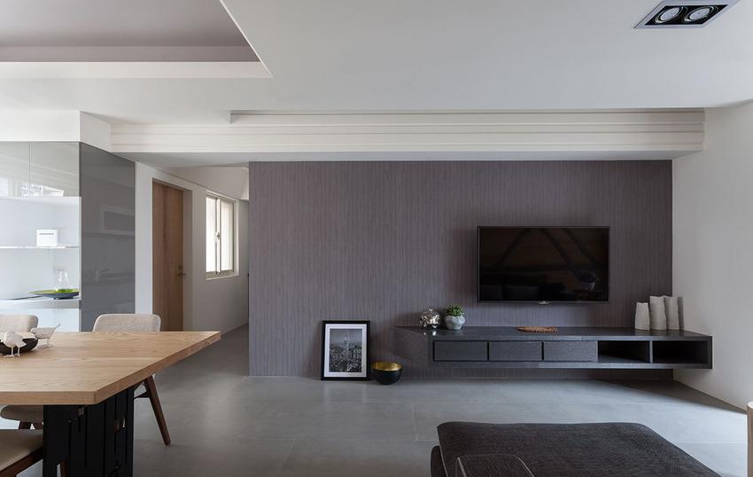 透过相近的颜色拉出一条横向视觉轴线,从电视墙往最左边延伸到具斜角设计的电器柜。