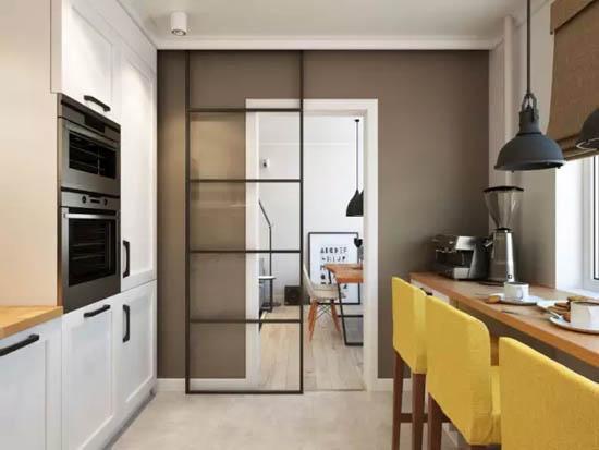 厨房的地砖与客厅的木地板被一道透明的黑框移门相隔,实现分区。