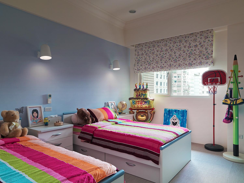 儿童房摆置了两张小床,蓝色系的墙面以及花色的床品,给孩子一个欢乐愉快的场所