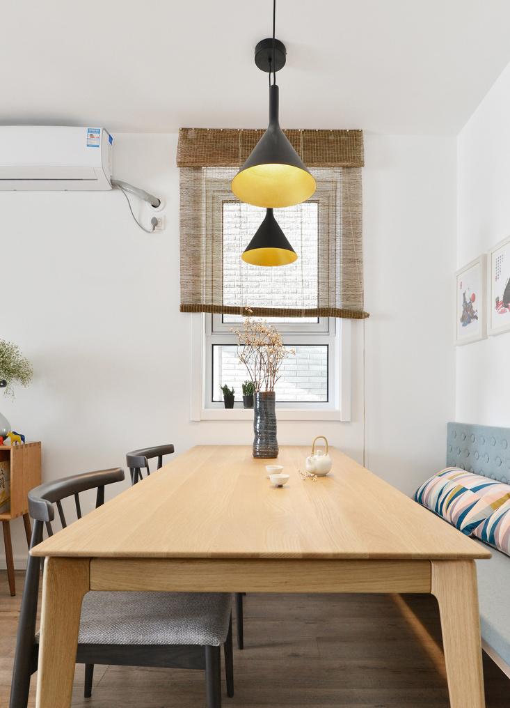 与窗户对称的餐厅格局,在卡座和原木的衬托下变得朴素自然,窗户的帘子也很有工匠感。