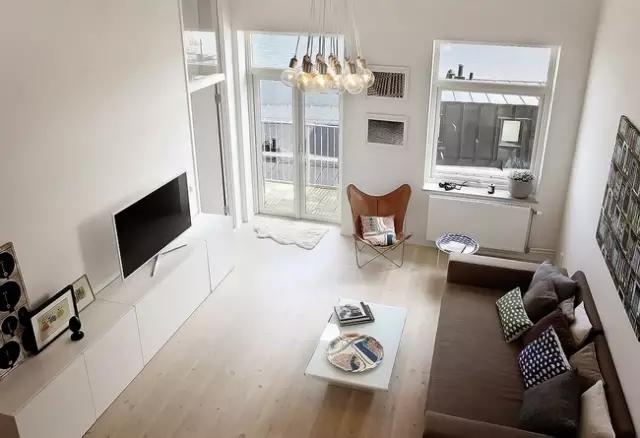 二层阁楼俯瞰一层的模样。地板的米黄色中和了大面积白色的单调,为屋子带来了生活的温度和气息。