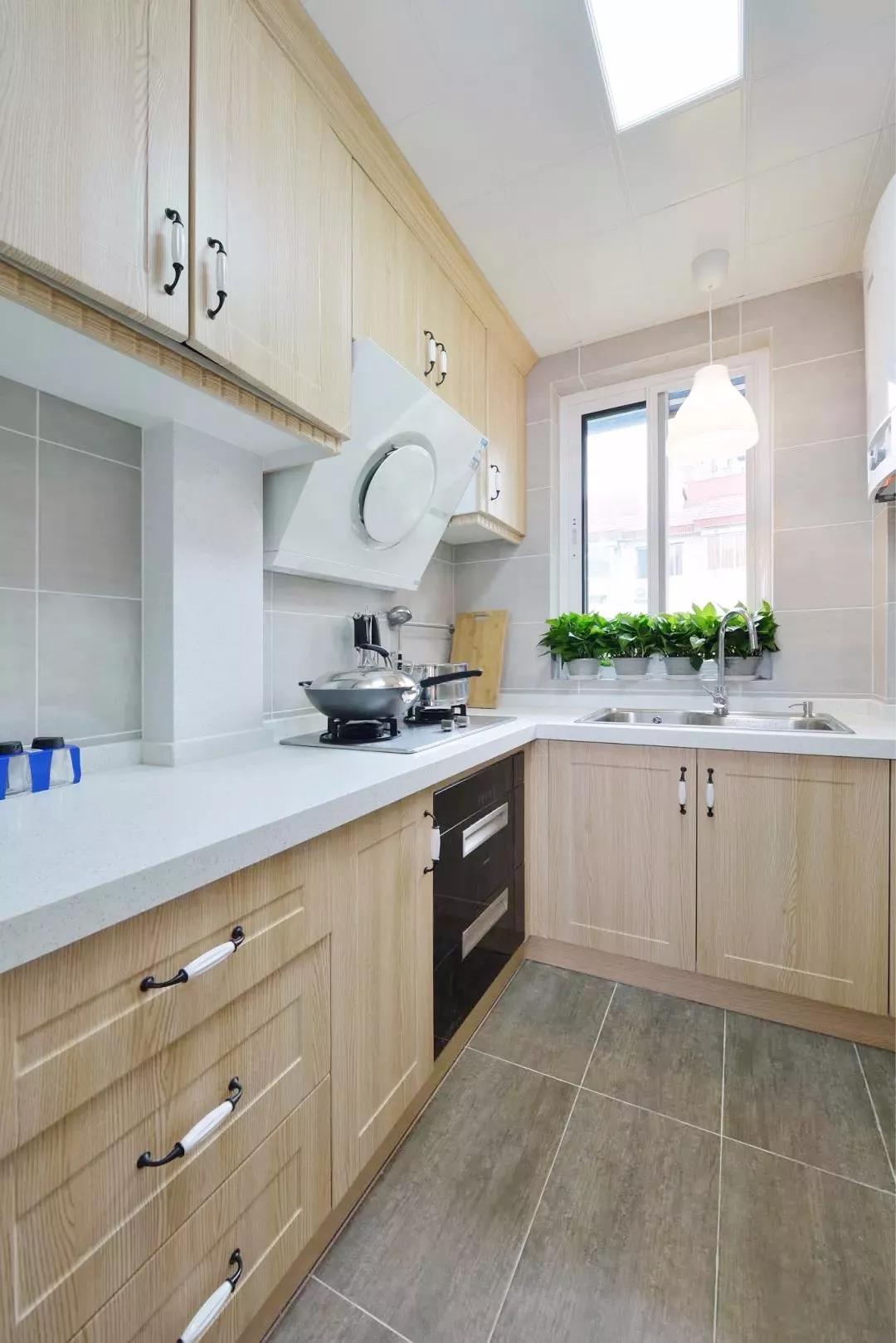 厨房同样采用了原木色橱柜,光线透过窗直射室内,整个空间明亮干净。