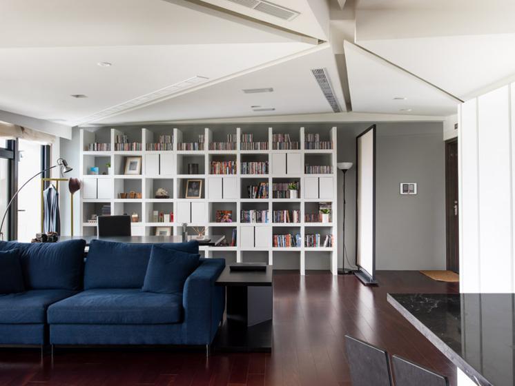 书房被布置在沙发后面,首先就被书柜空间的丰富所吸引。