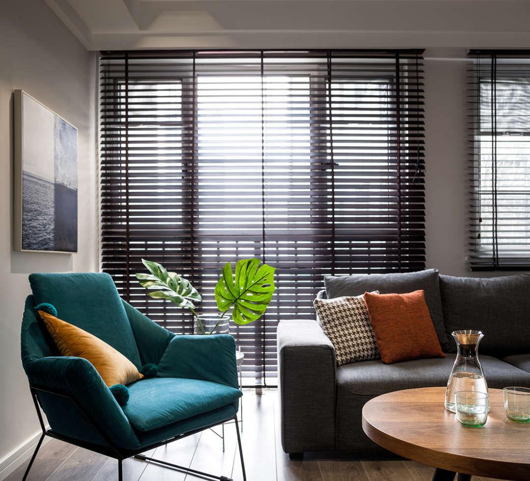 换个角度看客厅,用深色的百叶帘来营造空间的整体氛围的神秘感,胡桃木的色调也让空间多了几分小资的属性。