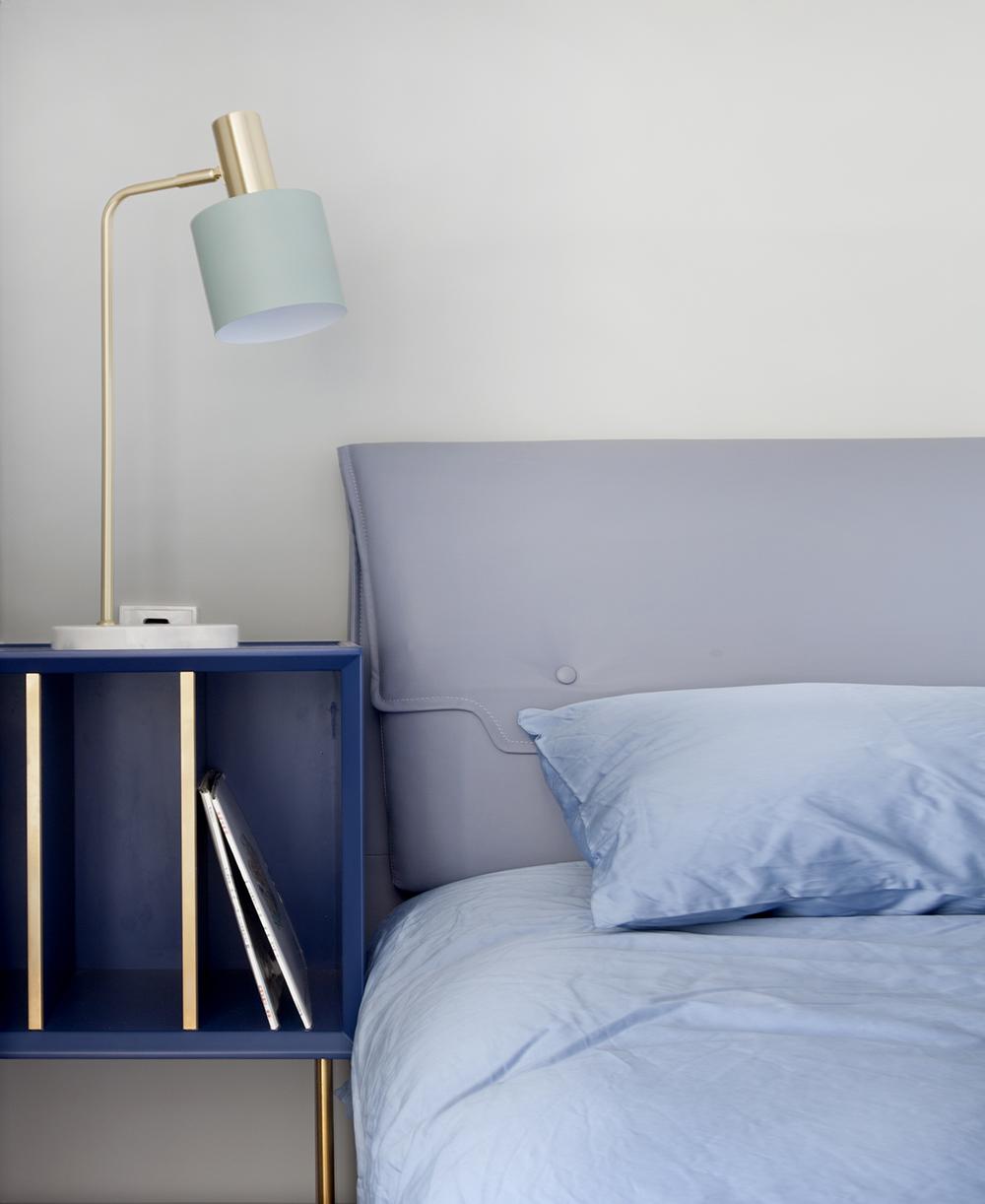 床头背景墙采用净色设计,尽显现代风格特色,蓝色床品让整个客厅空间充满雅致色彩。