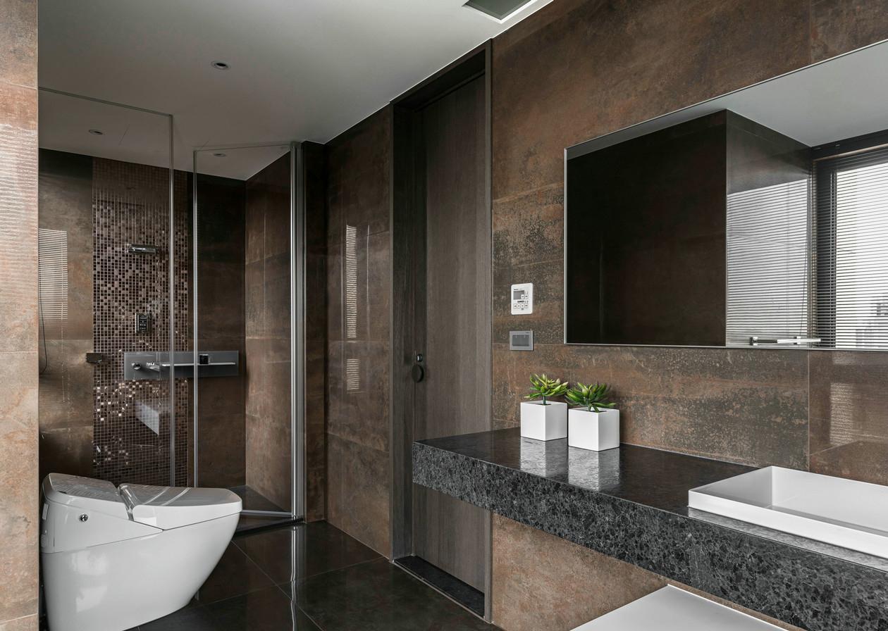 卫生间的布置比较简约时尚,大理石的洗手台搭配镜子,台面上再摆上一株绿植更显活力。