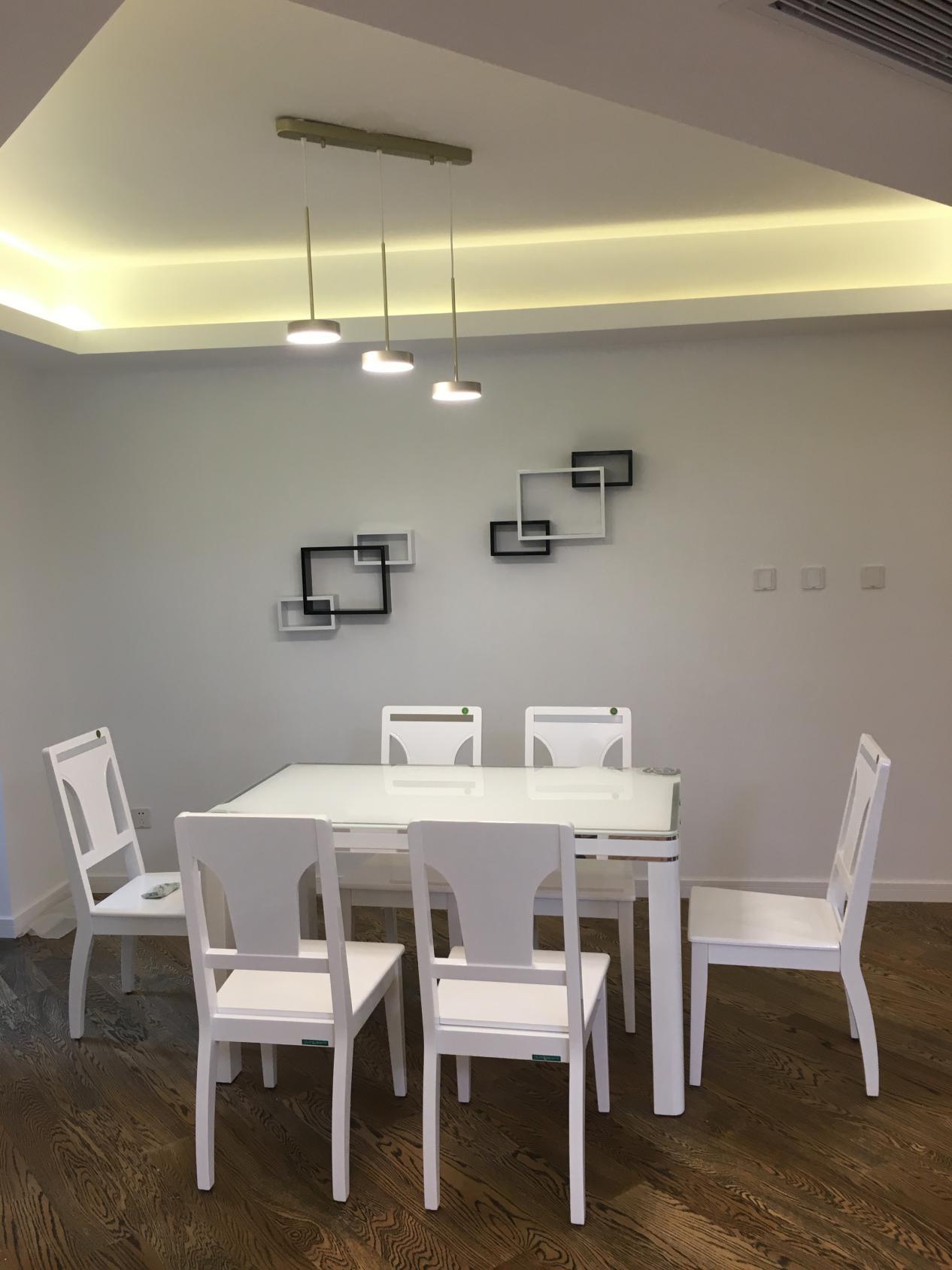简单的餐厅里,这套纯白餐桌餐椅非常乍眼,在上方三盏吊灯的照射下,让原本昏暗的餐厅变得明亮。