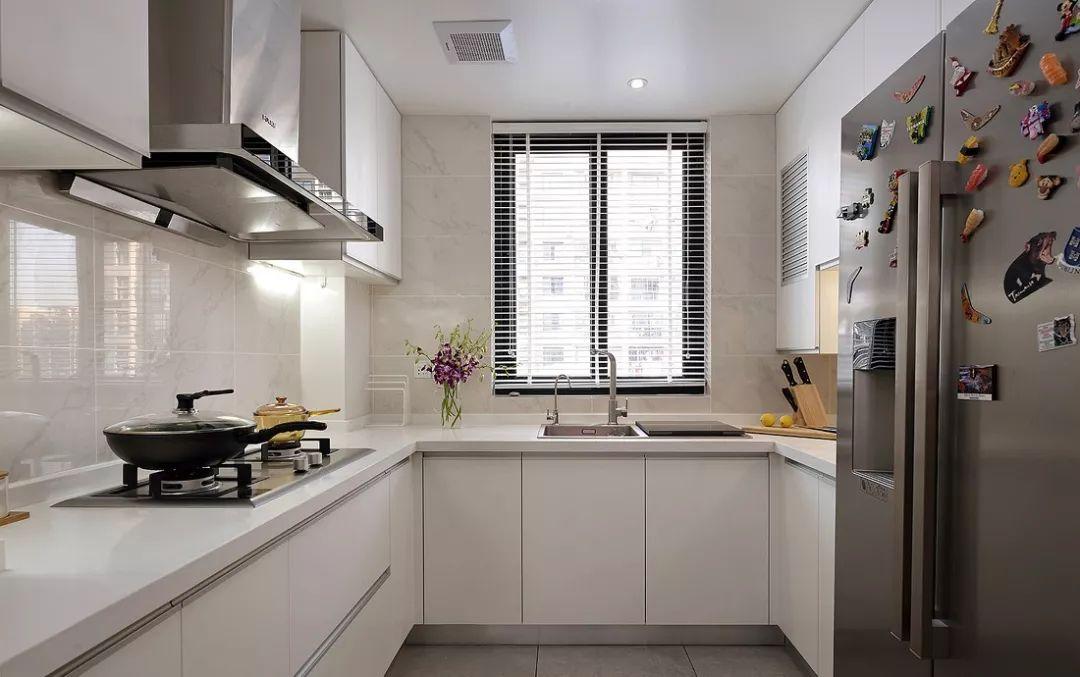 厨房U字形布局,提供丰富的收纳与储物空间。整体以白色为主调,干净敞亮。