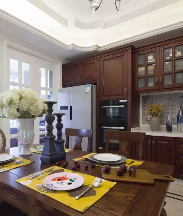 在餐桌椅的另一侧是到顶的餐边柜,满足了鞋柜的需求,也承担着酒柜的作用,冰箱和一些厨房电器更是嵌入其中