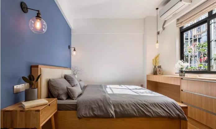 主卧木色地面搭配木色家具,一面星空蓝背景点缀两盏玻璃壁灯。