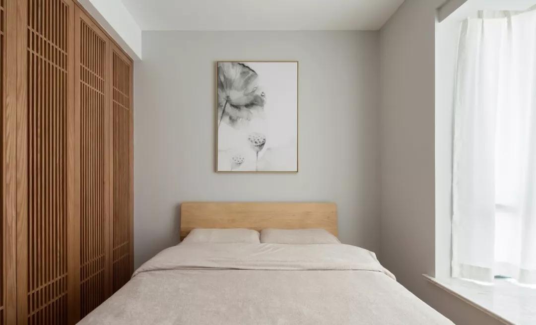 次卧并没有过多的装饰,床头背景墙上以一幅莲藕水墨画装点,韵味十足。
