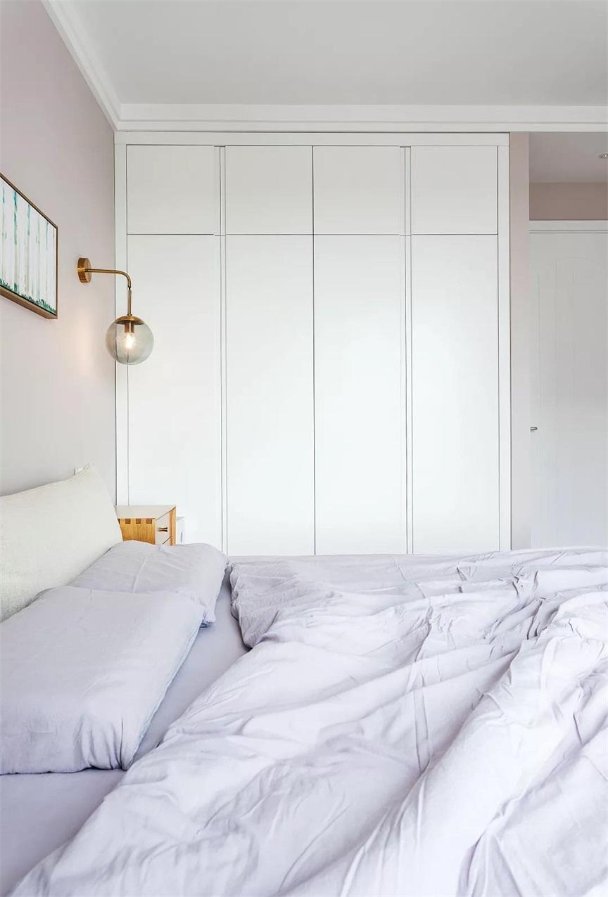 側臥空間采用白色背景打造,嵌入式衣櫃提升了空間質感,淺紫色床品爲空間注入了一絲浪漫。