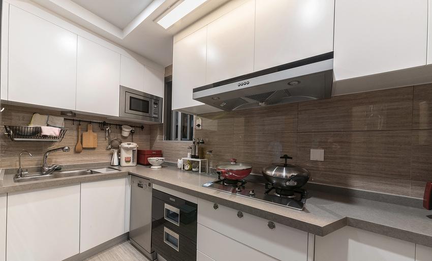 以白色橱柜搭配原有科技感木纹砖,让厨房呈现简约利落感。