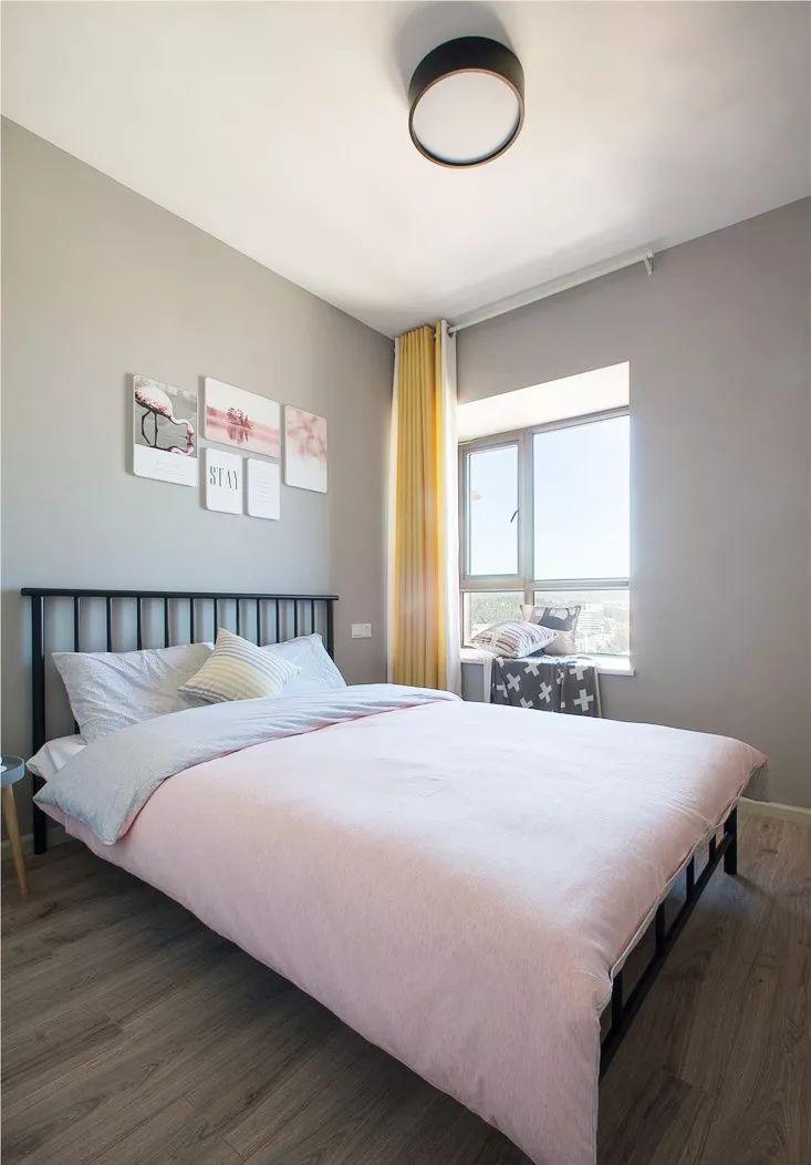 次卧与主卧的风格相得益彰,灰色的墙面加黑色的铁艺床,粉色的装饰画与床品,恬静温馨。