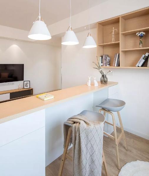 一道原木色矮墙吧台作为沙发墙,这样让空间整体的通透性更加强烈明显。吧台一侧敞开式置物柜与插座。