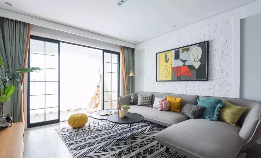 沙发背景墙采用白色文化砖铺贴,加以个性挂画进行点缀;为空间增加一丝艺术气息;沙发的各色抱枕增添活力。