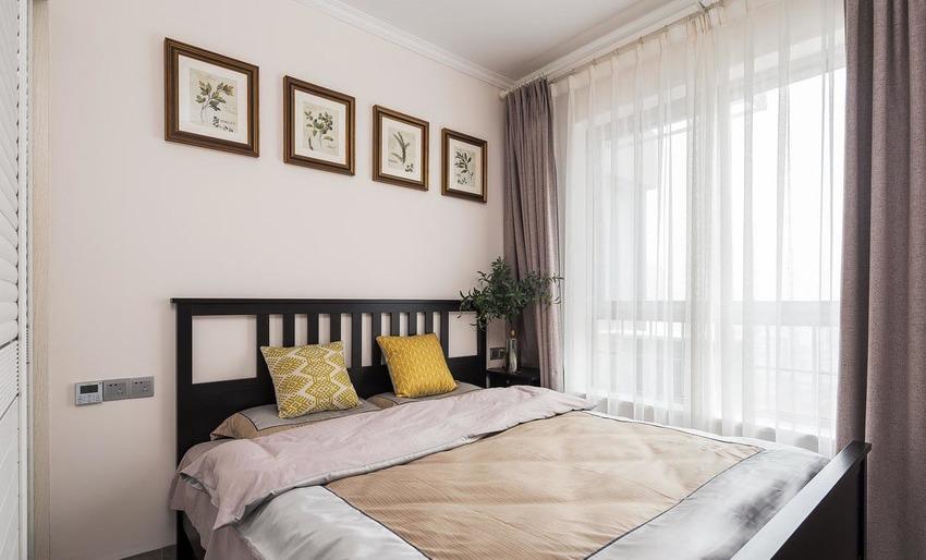 次卧浅粉色乳胶漆墙面,点缀几幅绿植装饰画作床背景,黑色简约大床与小巧的床头柜,咖啡色窗帘,空间清雅。
