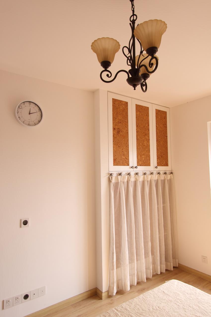 卧室里内嵌的柜子也同样使用了木色作底,自然质朴的同时,配合纱帘又流露出一丝柔软。