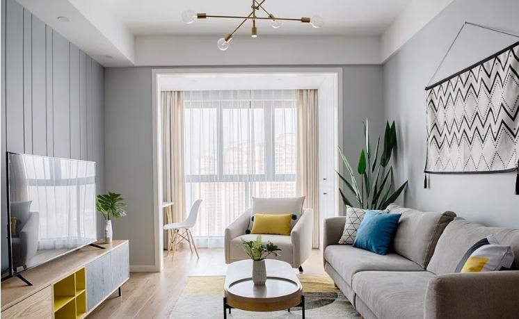 客厅宽敞明亮,以白色和浅灰色为空间基调,辅以柔和色调的软装进行点缀,营造温馨惬意的氛围。