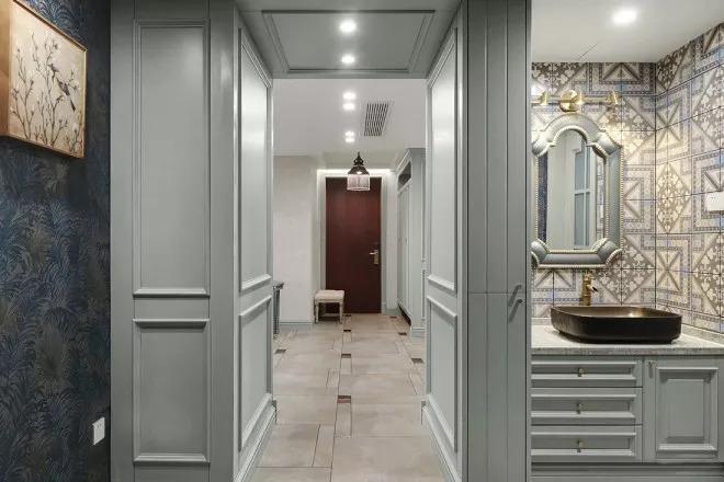 灰色饰墙板包裹整个过道墙面,简单的造型展现优雅的欧式气质。隐约瞥见客卫一角。