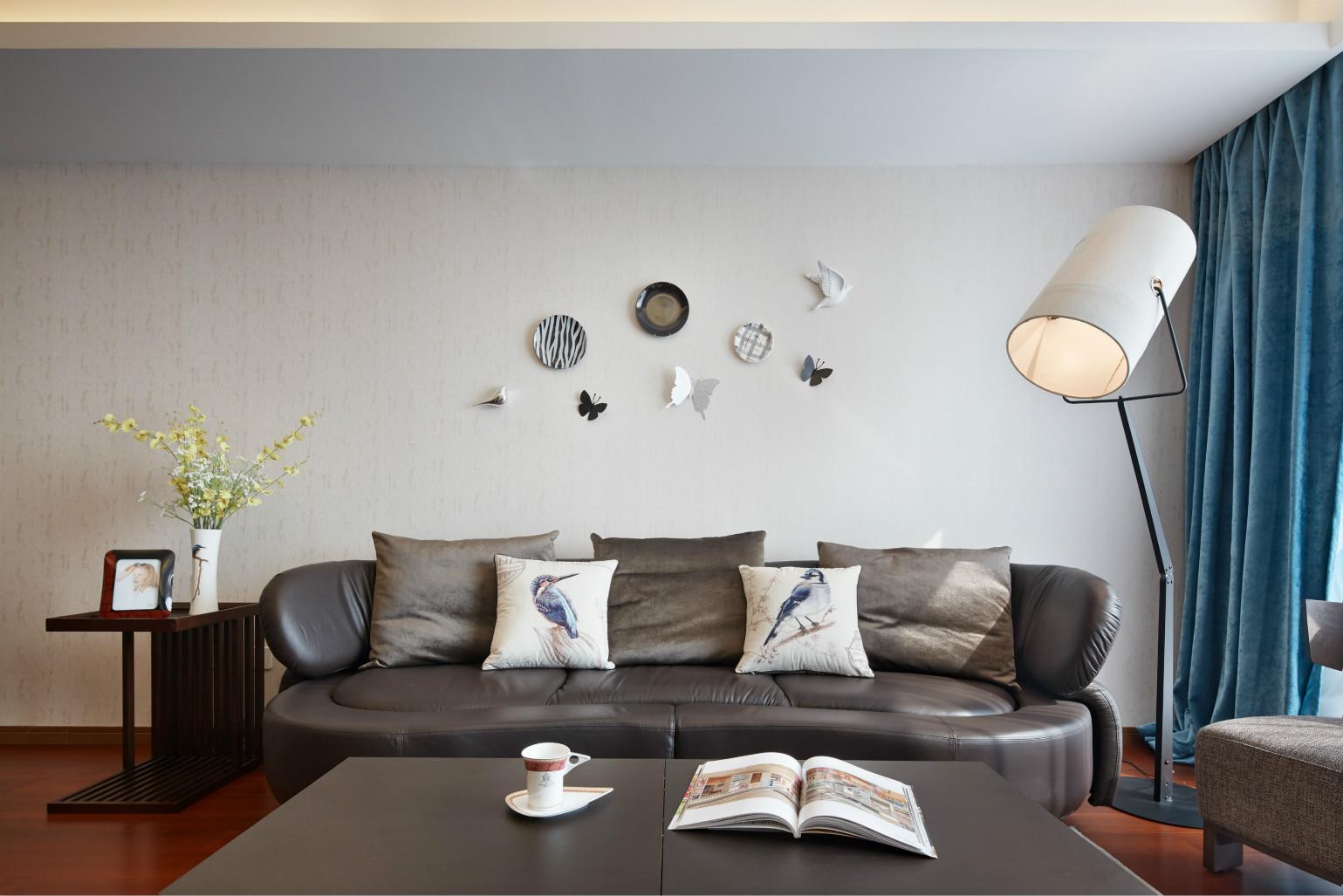 沙发的背景墙挂着艺术气息的碟子,使整个客厅含有艺术氛围