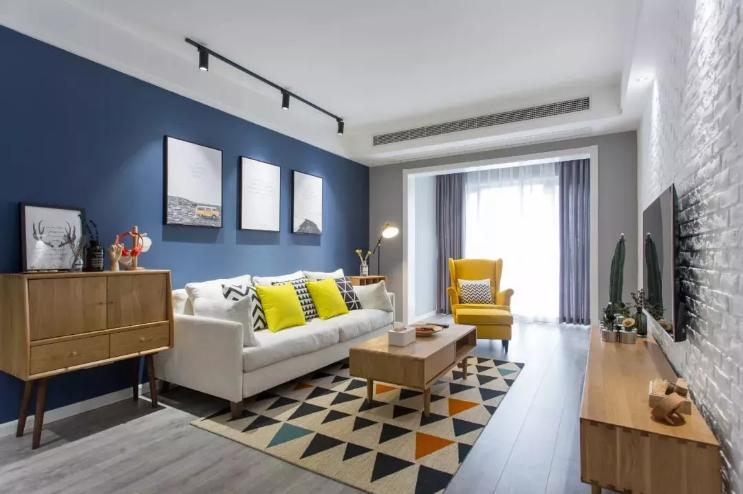 客厅沙发墙刷深蓝色漆,再搭配一组简约的挂画装饰,顶上导轨射灯的照射下,显得特别耐看。