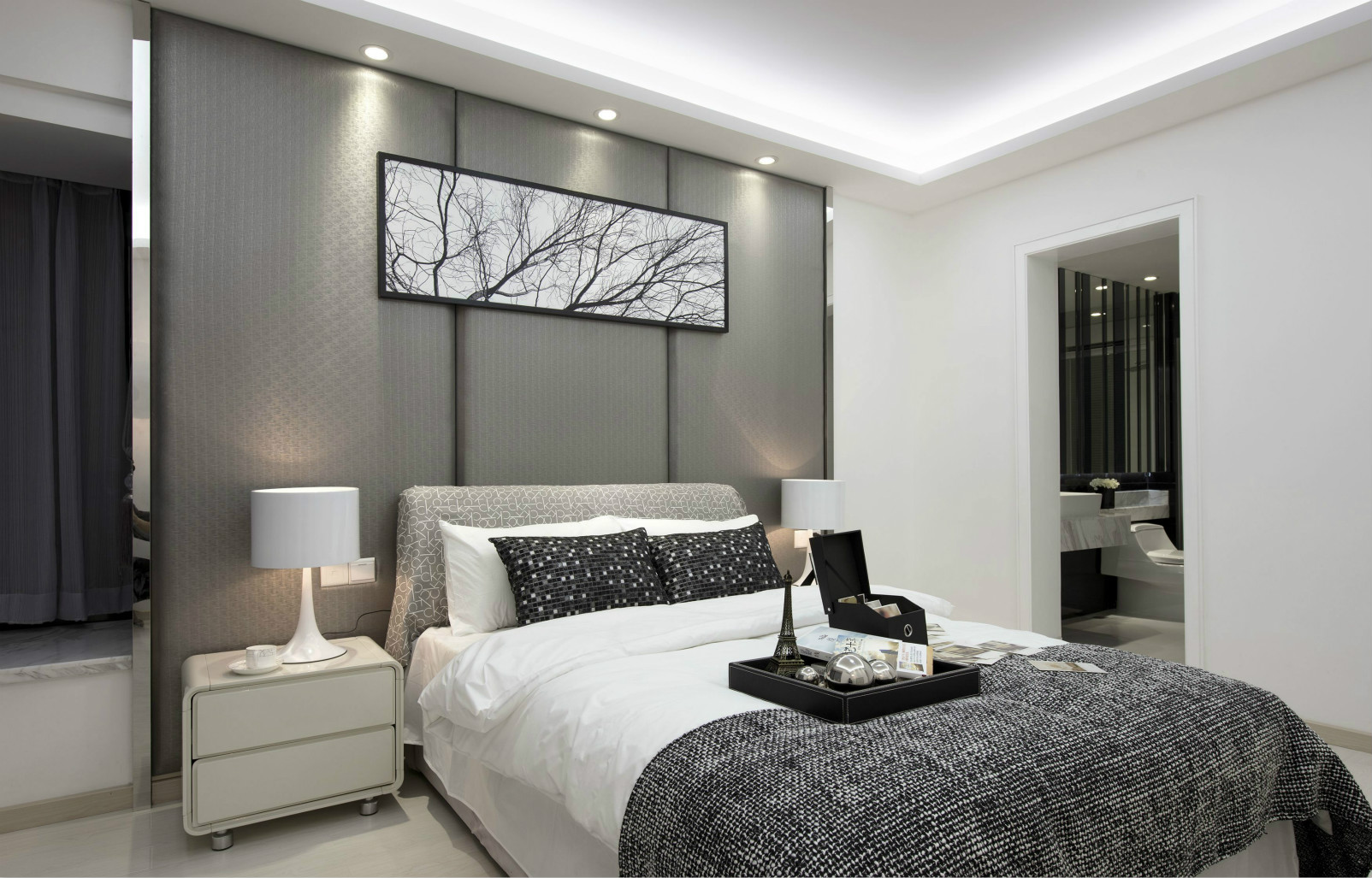 卧室中放置着简约的大床,搭配上白灰色的布艺床品,很是简约雅致。