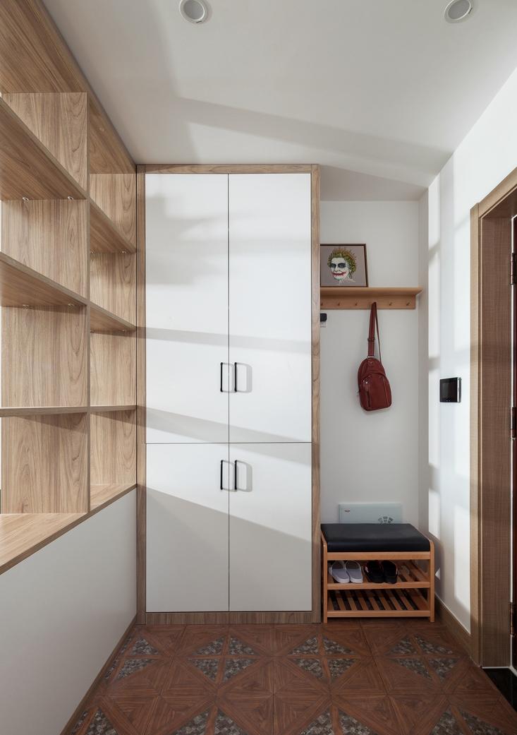 拼花木纹砖丰富入户层次感,柜体可作为鞋柜,又能充当隔断作用,上部敞开式设计,使客厅光线得以延伸。