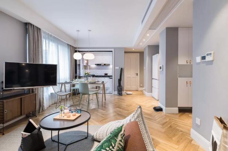 客厅的整个色调分为三个部分,墙面的浅灰,吊灯的纯白,地板的木色。地板用拼接方式拉伸了客厅的纵深感。