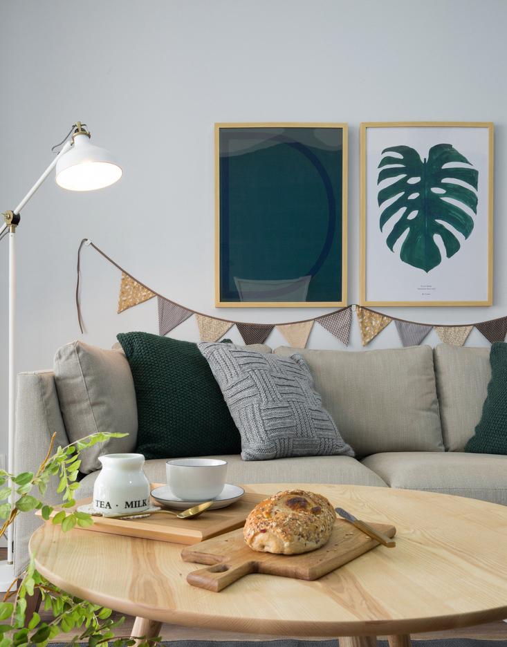 布艺沙发和挂画的自然配色,让现代落地管式小台灯显得雅致小巧。