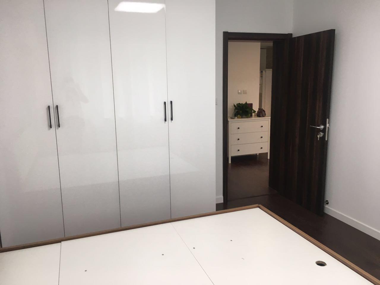 卧室色调延续整体风格,虽然选用深色系的爱空间标配的内门和地板,但定制的白色的大衣柜因为自带镜面效果。