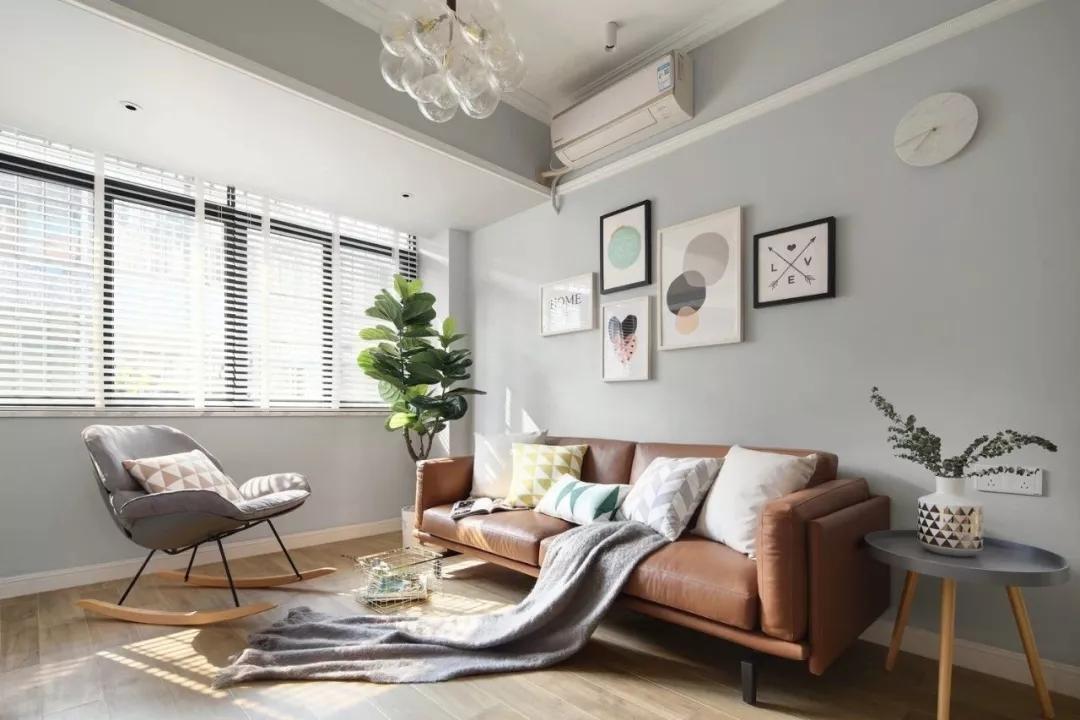 棕色皮质沙发增加质感,与地板相呼应;客厅舍弃了茶几,不会让空间显得拥挤。