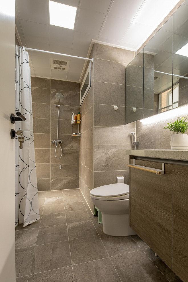 卫生间墙面和地板以灰色为主,墙顶照灯及通透的玻璃镜面,使整体显得敞亮、明净。