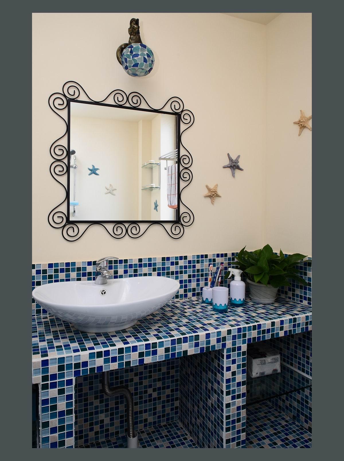 卫生间的花边状镜子简单又时尚,墙上的海星装饰了墙面的空白。