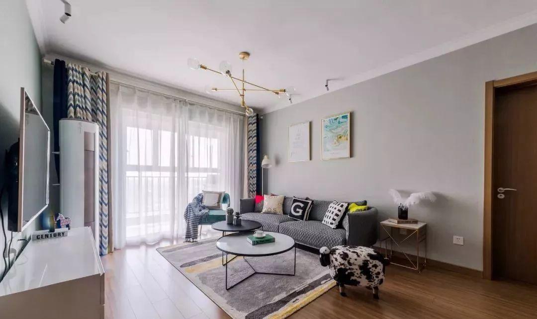 客厅延续木色地面,极简顶面装一盏后现代吊灯,金色元素穿插整室。