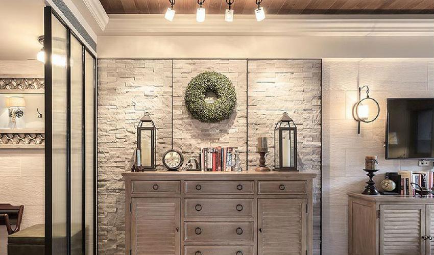 墙面铺贴天然石材瓷砖,作为进入室内的第一视觉焦点,摆放半高柜,穿鞋椅与玻璃隔器屏。