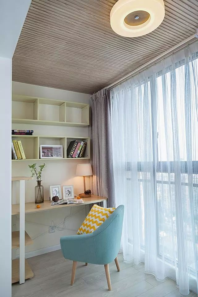 阳台部分做了木质的吊顶,这边被规划成了书房,上方是格子书架,底下是书桌,旁边就是大大的落地窗。