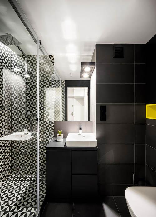 浴室在淋浴间搭配黑色和白色图案的瓷砖,在其余的空间内装有大的黑色瓷砖。