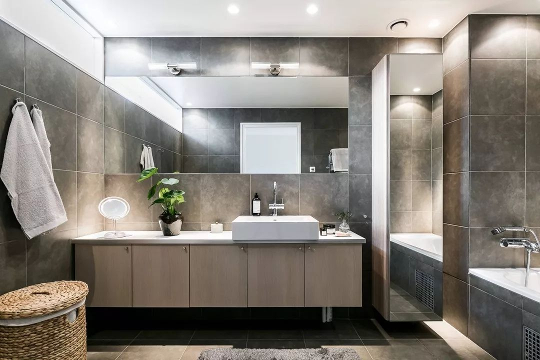 卫生间的四周都铺了灰色的瓷砖与地面一致,洗漱台的柜子很好的解决了卫生间的储物问题。