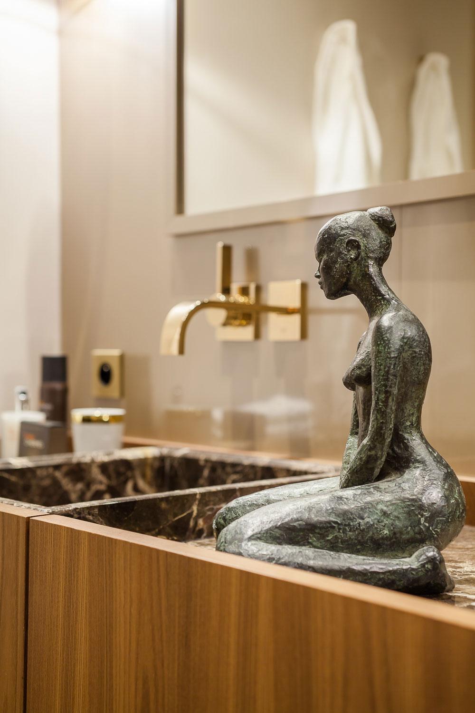 卫生间的洗手台放置了艺术的精致的小铜人,艺术感足足。