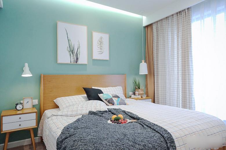 主卧更加突出了清新的感觉,床和床头柜就是最常见的北欧风。整个卧室没有一丝深色,室内变得明亮温暖。