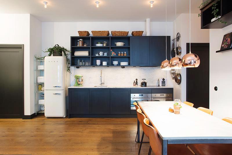 厨房被放在墙边,尽可能低的占用空间,深灰色橱柜非常显格调。