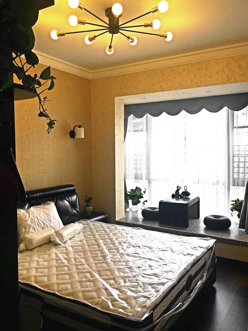 主卧暖黄色的花纹墙纸,更显温馨,增加了休憩的舒适感。