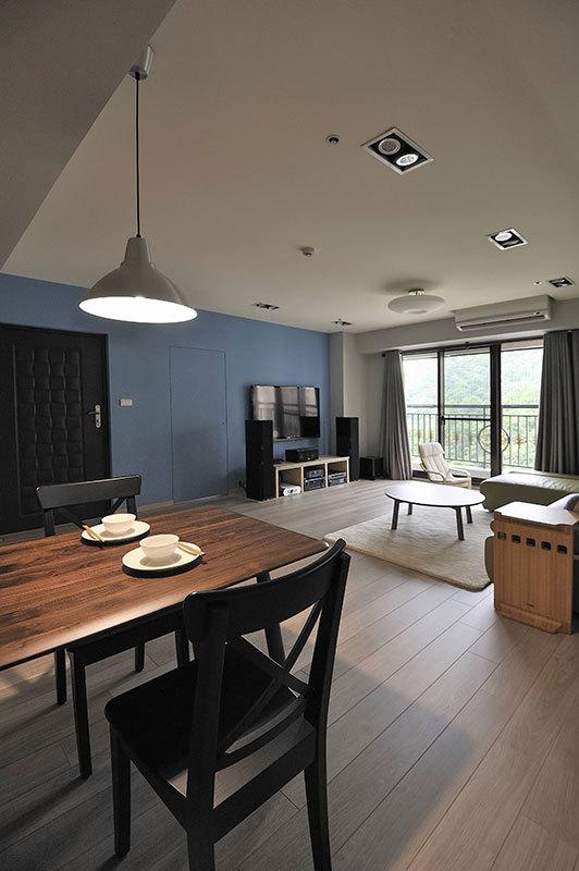 木色温暖中,皮质柔软的嫩绿色沙发,与灰蓝色调的电视牆,设计师结合小朋友喜爱的颜色,与窗外的绿光日景,