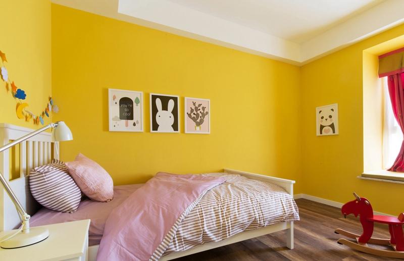 女儿房则用大面积黄色墙面加挂画的设计,让空间变得灵动。