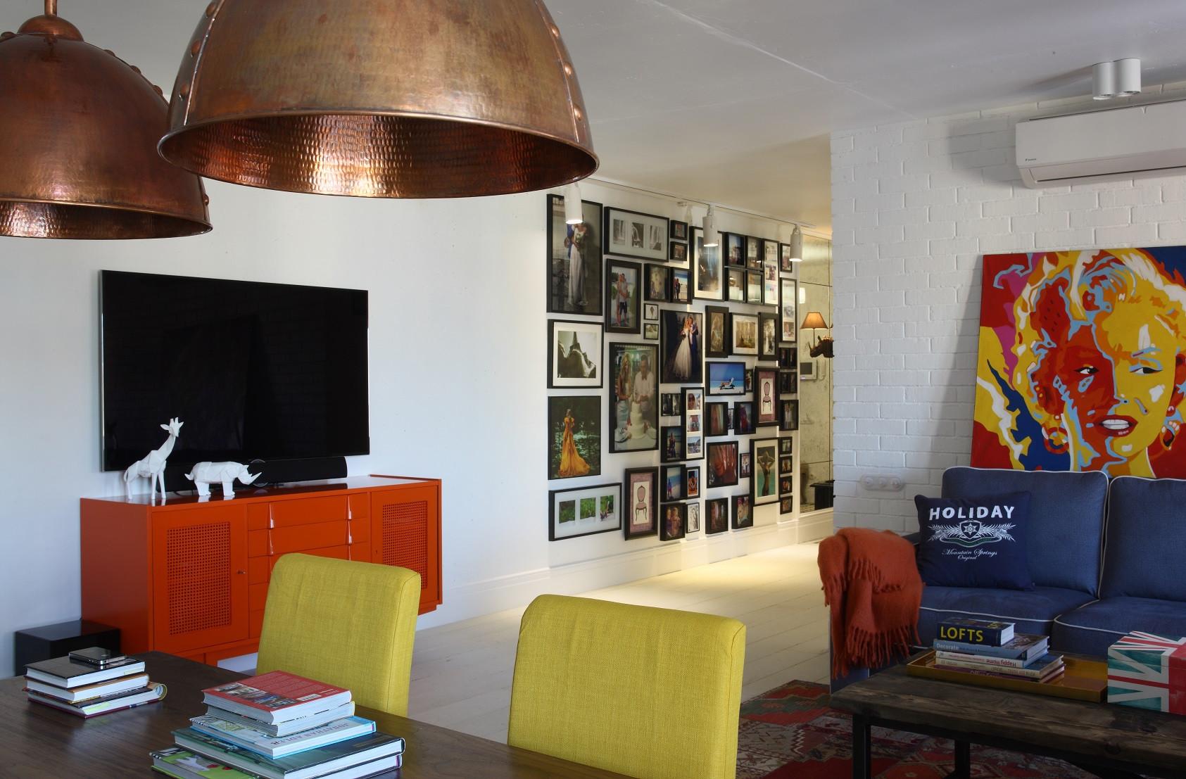 做了精致的木质电视柜,也更好的收纳,墙壁侧面挂了很多画像,很有艺术气息